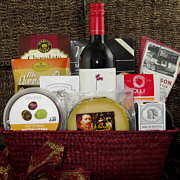 wine basket with cheese, salami, olives, chocolate and other foods