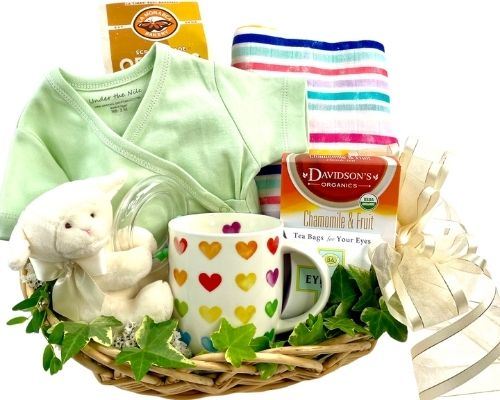 a basket with a Mug, Tea, Madeleines, Chocolate for Mom, a Muslin Blanket, Booties, Organic Cotton Baby Doll and Lullaby CD