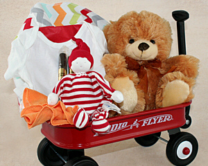 A small Radio Flyer red wagon filled with a receiving blanket, baby outfit, stuffed animal, soft washcloth, and a little sweet for mom