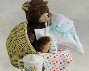 a bassinet shaped basket with a plush bear, flannel blanket, cotton onesie, bib, oatmeal bath soak and more