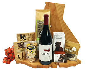 a California shaped Cutting Board holds a fine wine, Olive Oil and Sea Salt Popcorn, caramels, John Kelly Fudge truffles and more