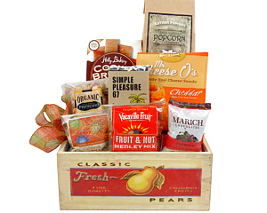 a fruit crate holds Cookie Brittle Butter Cookies, Brown Sugar and Maple Popcorn,Chocolate Bar with Hazelnuts and Salt, nuts and more