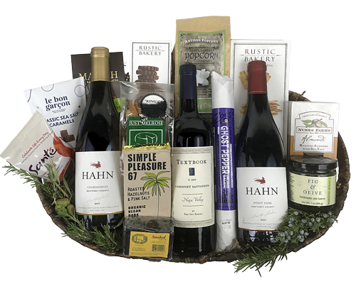 a large wicker basket with three California wines, cheese, crackers, chocolates, salami and more all laying down and seen from above