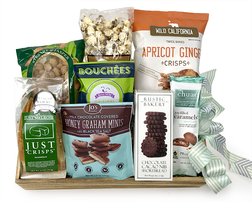 a wood tray has Rustic Bakery Cacao Nib bars, Ma & Pa chocolate drizzled popcorn, salsa, almonds, Bond Bar Chocolate and more CA treats