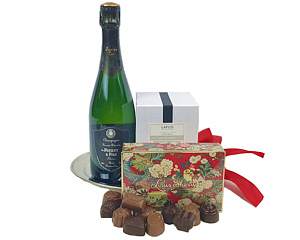 on a silver serving tray we see a bottle of Veuve Fourny Grande Reserve Champagne, Louis Sherry Chocolates and a LAFCO Luxury Candle