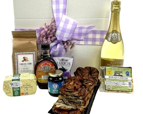 Box filled with Champagne, sweet bread, jam, butter, nut mix
