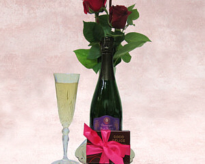 a bottle of Prosecco on a tray with a box of chocolates and a small flower arrangement