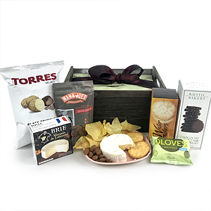 a basket with cheese, crackers, sweets an other foods