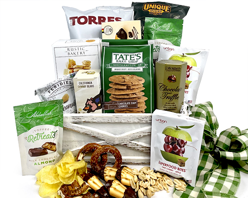 a wicker basket with cookies, chocolate and snacks in a green motif