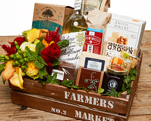 A wooden crate with the words Farmers Market in stencil letters with the contents in the description.