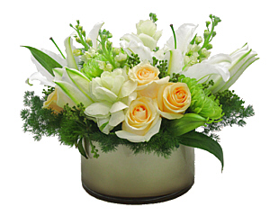 a champagne colored round vase with dark edges with white lillies, pale yellow roses and greens