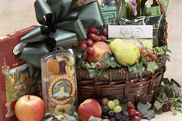 a basket with cheese, fruit, crackers and other fine foods as well as a flower arrangement or plant
