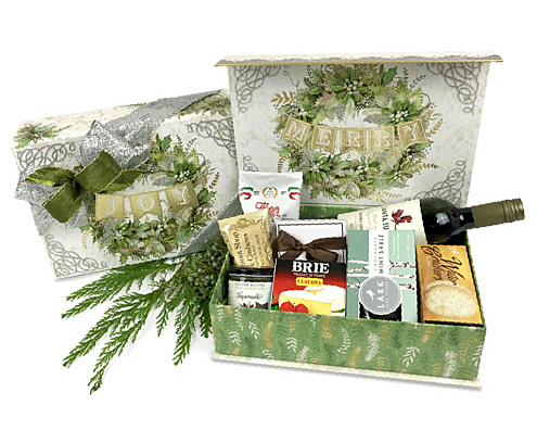 A beautiful box decorated in silver, gold and green filled with sparkling wine, cheese, cookies and a candle