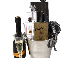 a metal champagne bucket holding prosecco, sparklers, cookies, snack mix and chocolate