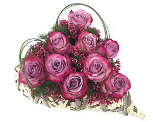 a heart-shaped wicker container with purple roses