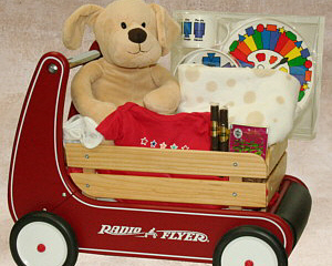 a wooden Radio Flyer Walker Wagon (it has a bar on back to help a baby learn to walk) with stuffed animal and things for a newborn