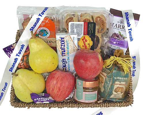 a wicker basket with fresh fruit, a bottle of soda, chocolate cookies and other items - all Kosher