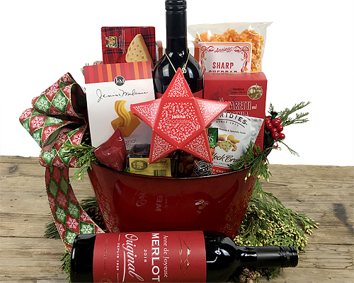 Red container filled with wine, cheese, chocolates, cookies and nuts
