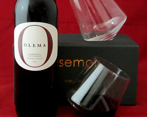 two Sempli wine glasses shown with their box and a bottle of red wine