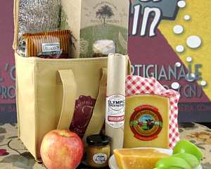 An insulated tan tote with the Fancifull logo shown with cheese, apples, salami, and boxes of other food sticking up out of the tote.