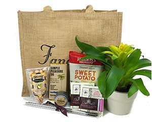 a Fancifull tote shown with a live plant, nuts, chocolate, chips, tea, a candle and metal straws