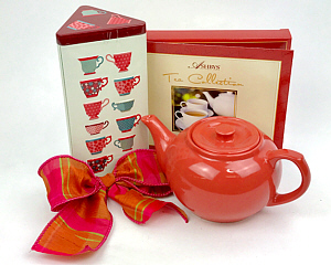 an orange teapot is shown with a tall triangular tin of English tea cookies an a gift box of assorted teas
