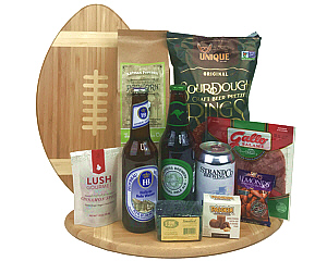 a football shaped cutting board with 3 beers, salami, nuts and other snacks