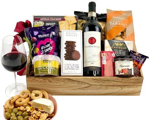 a wine basket with cheese, salami, olives, chocolate and other foods all lying down